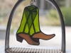 Stained glass pair of riding boots hanging in a stirrup