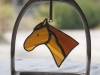 Stained glass horse ornament hanging in a stirrup