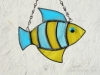 """Made of light blue wispy and yellow wispy glass. Eye is a light blue wiggle eye securely glued on. Finished in a pewter patina. Measures 4 3/4 """" wide by 4"""" tall. Fish in this pattern are $15 each."""