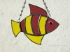 """Made of hammered yellow and rough roll cranberry glass. Eye is a pink wiggle eye securely glued on. Finished in a pewter patina. Measures 4 3/4 """" wide by 4"""" tall. Fish in this pattern are $15 each."""