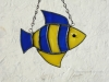 "Made of dark blue wispy and yellow wispy glass. Eye is a yellow wiggle eye securely glued on. Finished in a pewter patina. Measures 4 3/4 "" wide by 4"" tall. Fish in this pattern are $15 each."