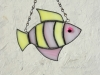 "Made of translucent yellow and pink wispy glass. Eye is a pink wiggle eye securely glued on. Finished in a pewter patina. Measures 4 3/4 "" wide by 4"" tall. Fish in this pattern are $15 each."