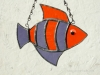 """Made of purple and orange rough roll glass. Eye is an orange wiggle eye securely glued on. Finished in a pewter patina. Measures 4 3/4 """" wide by 4"""" tall. Fish in this pattern are $15 each."""