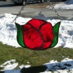 Single red tulip bulb in stained glass