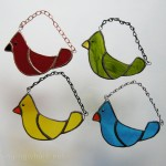 Small stained glass birds in red, yellow, green, and blue.