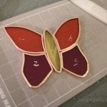 Red/orange/yellow butterfly cut and foiled, about to be soldered together.