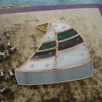 Stained glass sailboat after being cut and foiled.